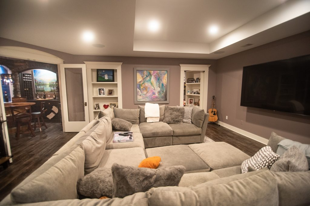 basement living room with large sectional and bookcases