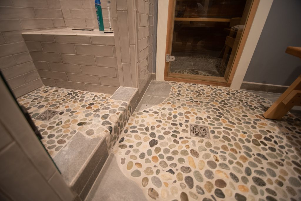 tile flooring in shower from rectangular tiles mixed into rock tiles
